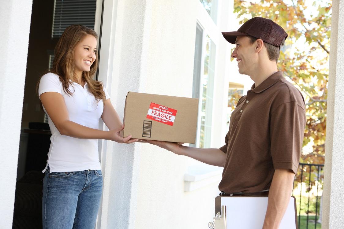 Frau an Haustür mit Paketbote